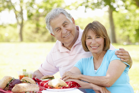 parejas amandose: Pares hispánicos mayores que disfrutan de comida campestre en el parque