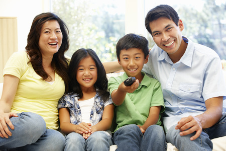 Familia asiática ver la televisión
