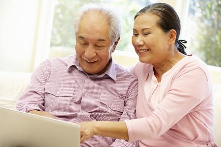 Pares asiáticos mayores usando la computadora portátil Foto de archivo