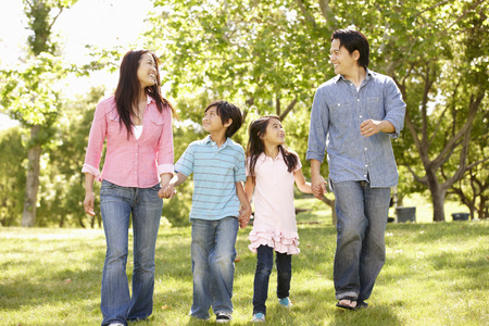 holding family together: Asian family walking hand in hand in park