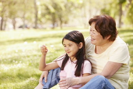asian trees: Asian grandmother and granddaughter blowing bubbles in park