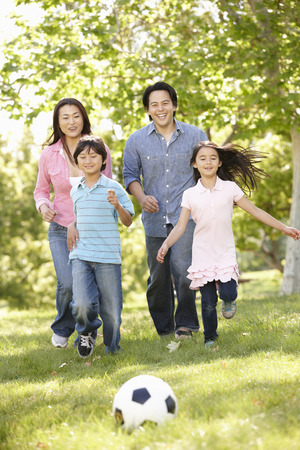 asian trees: Asian family playing soccerl in park Stock Photo
