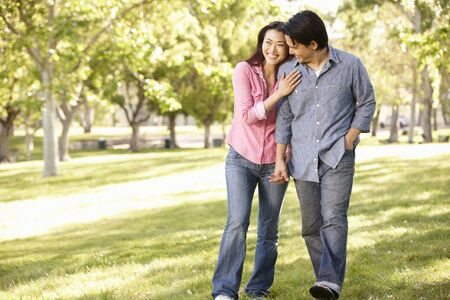 walk in the park: Asian couple walking hand in hand in park Stock Photo