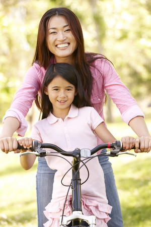 old asian: Asian mother and daughter on bicycle in park