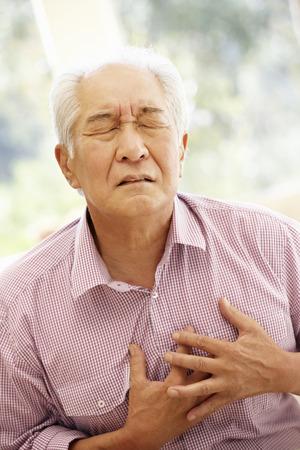 Senior Aziatische man met pijn op de borst