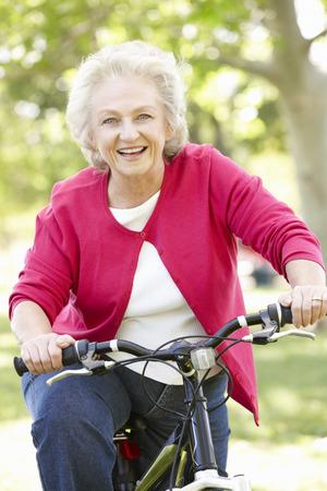 one senior adult woman: Senior woman riding bike