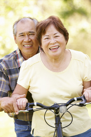 both: Senior Asian couple both sitting on one bike in park