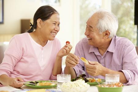 pareja comiendo: Mayor asiático comida compartir pareja en el hogar Foto de archivo