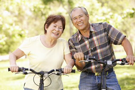 asian trees: Senior Asian couple riding bikes in park