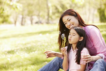 アジアの母と公園でシャボン玉を吹く娘 写真素材
