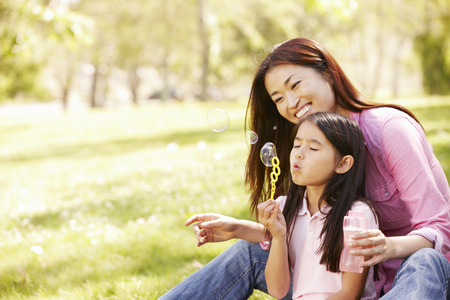 woman blowing: Asian mother and daughter blowing bubbles in park