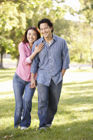 asian trees: Asian couple walking hand in hand in park Stock Photo
