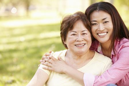 Madre asiática y adultos retrato hija al aire libre