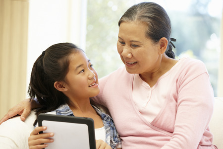 woman on couch: Senior Asian woman and granddaughter with tablet Stock Photo