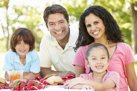 Familia hispana joven que disfruta de la comida campestre en el parque Foto de archivo - 42108920