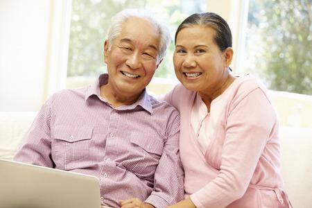 senior asian: Senior Asian couple using laptop
