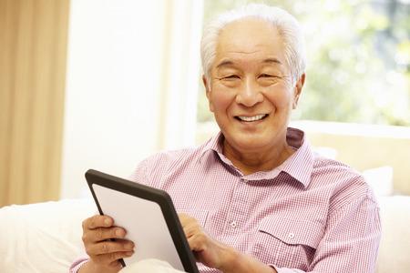 Senior Aziatische man met behulp van tablet