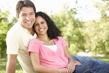 Romantic Young Hispanic Couple Relaxing In Park Stock Photo