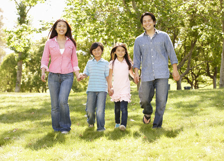 asian trees: Asian family walking hand in hand in park