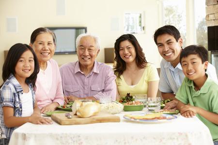 自宅の食事を共有するアジアの家族 写真素材
