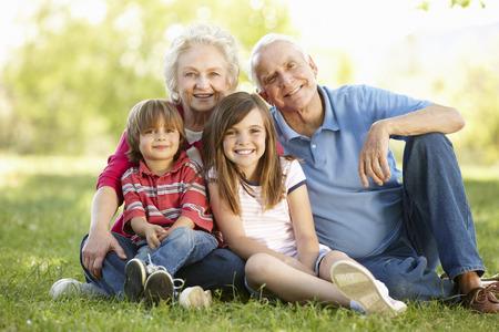 granny and grandad: Senior couple and grandchildren in park Stock Photo