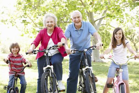 hombres maduros: Pares mayores con los nietos en las bicis