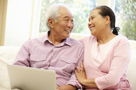 Senior Asian couple using laptop