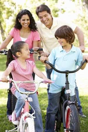 family outside: Young Hispanic Family Cycling In Park