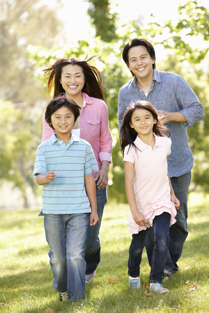 Asian mother and children running hand in hand in park Stock Photo