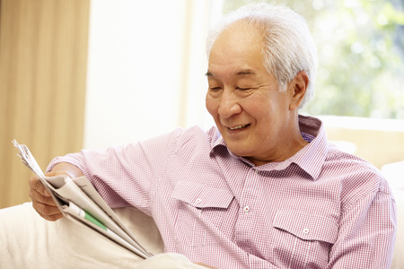 Senior Asian man reading newspaper Stock Photo