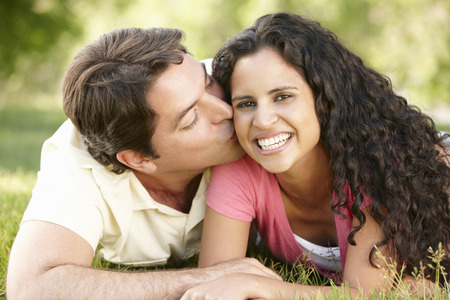 love kissing: Romantic Young Hispanic Couple Relaxing In Park Stock Photo