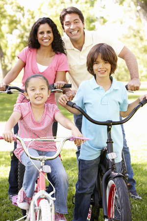 Young Hispanic Family Cycling In Park