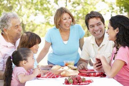 familia comiendo: Tres Pares hisp�nicos Generaci�n disfrutan de comida campestre en el parque