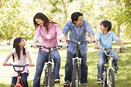 holding family together: Asian family riding bikes in park