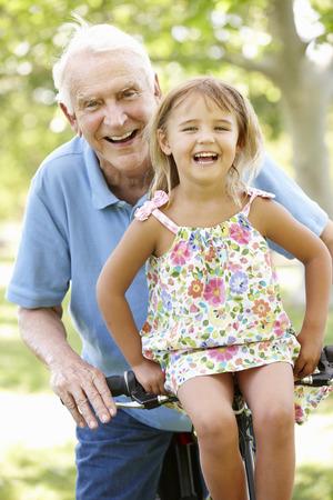 elderly people: Senior man riding bike with granddaughter
