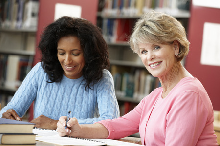 late sixties: Mature students working in library Stock Photo