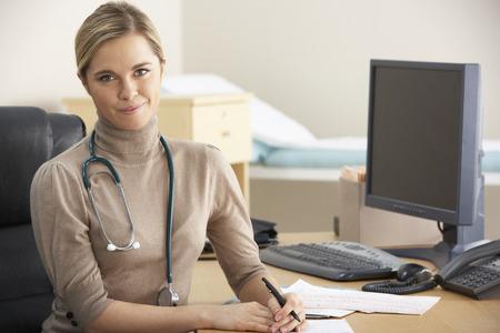 Vrouwelijke arts zitten aan de balie