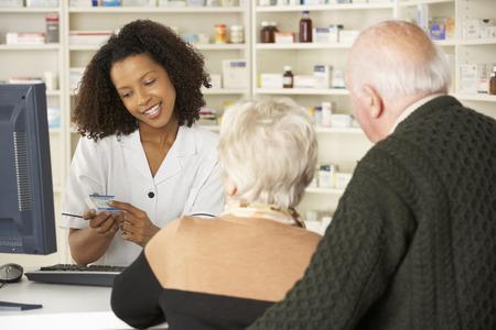 farmacia: Farmacéutico en la farmacia con pareja de ancianos Foto de archivo