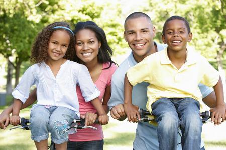 famille africaine: Jeune famille afro-américaine à vélo dans le parc