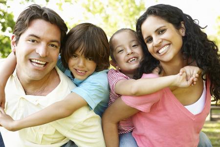 Young Hispanic Family Having Piggyback In Park
