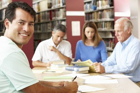 adult student: Mature students working in library Stock Photo