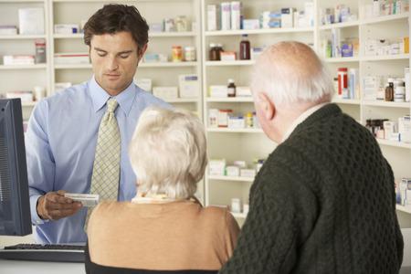 persona de la tercera edad: Farmacéutico en la farmacia con pareja de ancianos Foto de archivo