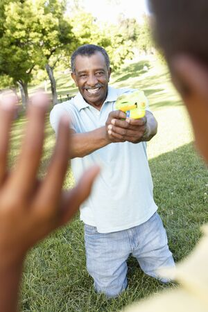 countryside loving: African American Grandfather And Grandson Playing With Water Pistols In Park
