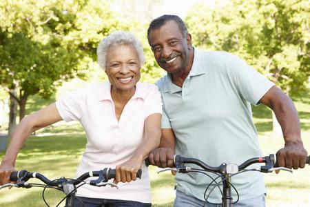シニアのアフリカ系アメリカ人カップルが公園でサイクリング