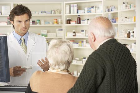 recetas medicas: Farmacéutico en la farmacia con pareja de ancianos Foto de archivo