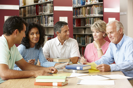 coursework: Mature students working in library Stock Photo