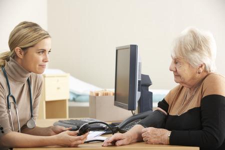 adult 80s: Doctor taking senior womans blood pressure