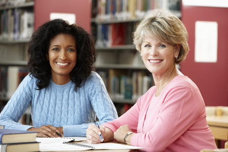 late forties: Mature students working in library Stock Photo