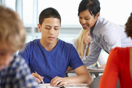 Profesor de ayudar a los estudiantes afroamericanos en clase Foto de archivo - 42118917