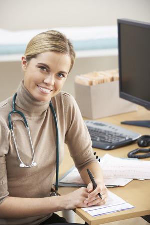 doctor female: Female Doctor sitting at desk Stock Photo